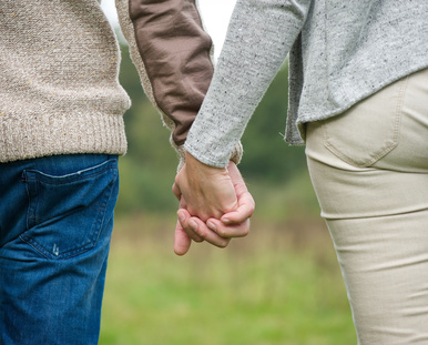 Male and female holding hands outdoors